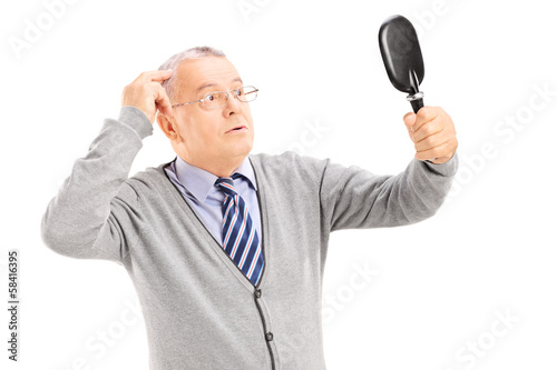 Middle aged gentleman checking for thinning hair in the mirror