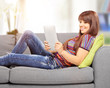 Young woman with tablet computer on sofa at home