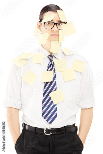Young man with tie covered in yellow notes