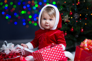 kid girl dressed as Santa Claus at Christmas tree with gifts