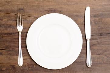 Weisser Teller mit Messer und Gabel