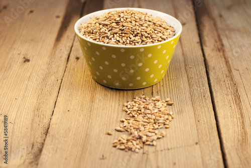 Barley in a bowl on a wooden background