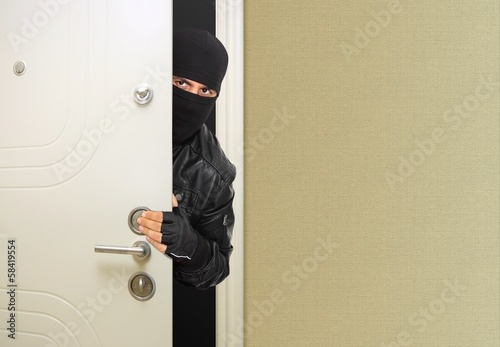 Masked thief at the entrance door
