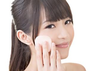 Beautiful asian woman using cosmetic sponge on face