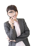 Young asian woman looking through a magnifying glass