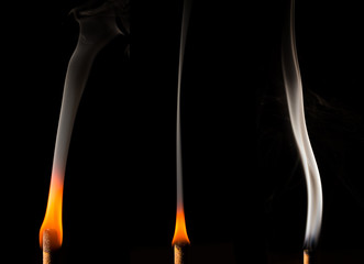 Burning candle with smoke on a dark background