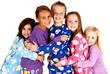happy children in winter pajamas hugging each other