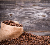 Sack of coffee beans on wood background