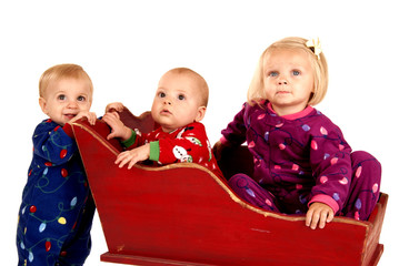 toddlers in Christmas pajamas sitting in a sleigh