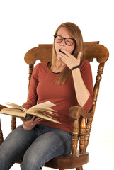 Student in rocking chair yawning while reading a book