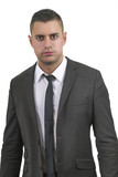 Serious looking young businessman in a suit (white background)
