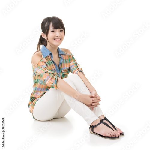 Happy smiling asian woman sit on ground