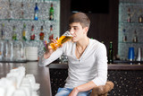 Young man drinking in a pub