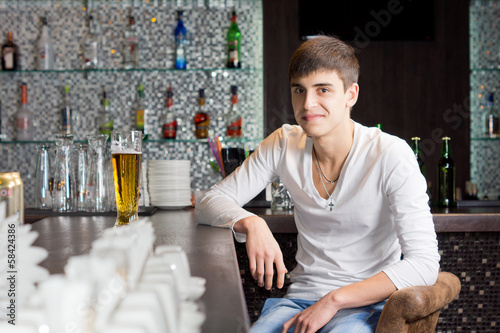 Friendly young man drinking in a bar