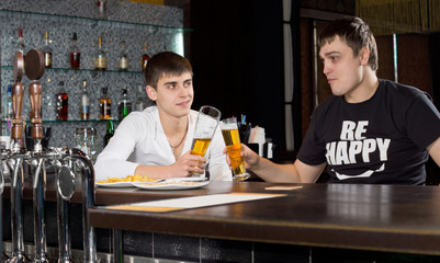 Two young men toasting each other over a beer