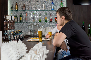 Two guys drinking at a bar