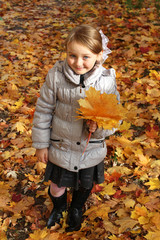 little girl with yellow leaf in autumn