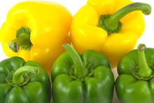 Two yellow and three green sweet bell peppers isolated