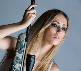 pretty girl in the studio with a rifle