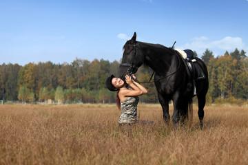 Piękna młoda dziewczyna bawi się z koniem.