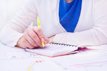 Business Woman Writing with pen in notepad