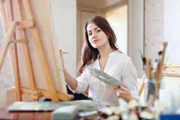 Long-haired young woman paints on canvas