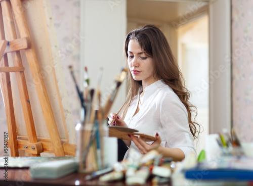 Long-haired woman   paints on canvas