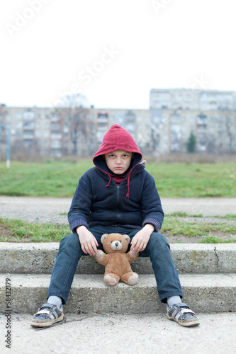 young homeless boy on the street with bear