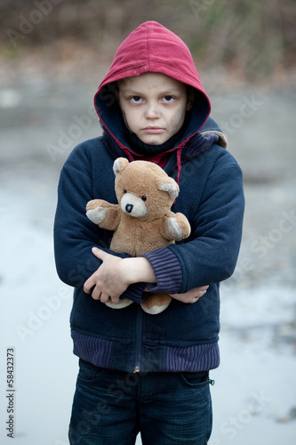 portrait of a homeless boy with bear