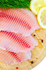 Fillets tilapia with lemon and dill on a round board