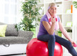 happy senior woman sitting on gym ball, and exercise