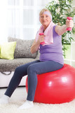Senior woman sitting on gym ball, and exercise with weights at h