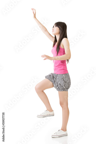Young asian woman climbing up the wall