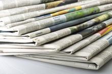 Pile de divers journaux sur fond blanc.