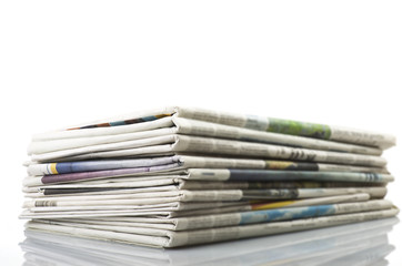 Pile of Various newspapers over white background.