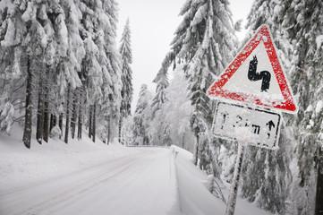 Schild an Straße warnt vor Gefahr wegen Schnee Eis