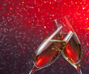 champagne flutes with gold bubbles on red light bokeh background