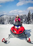Couple driving snowmobile