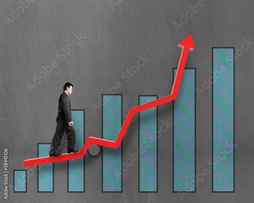 Businessman walking on growth red arrow with chart