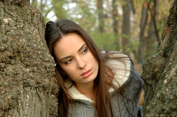 young woman peeking between two trees