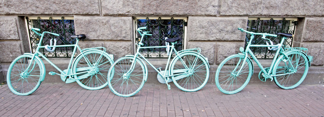 Three green bicycles against a wall in Amsterdam Netherlands