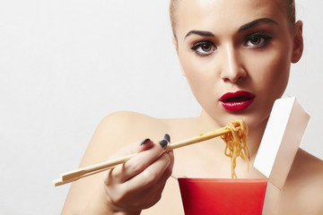 beautiful woman are eating noodles.red lips.Chinese sticks