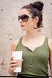 junge attraktive frau mit coffee to go und sonnenbrille
