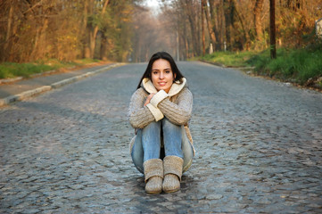 young woman sitting in the middle of an old road