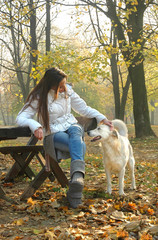 young woman sitting on bench in autumn park cuddling dog
