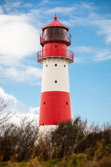 rot weisser leuchtturm vor blauem himmer wolken ostsee