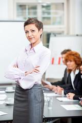Junge erfolgreiche geschäftsfrau lachend mit konferenz
