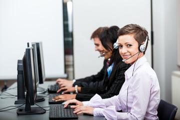 Callcenter Mitarbeiter mit Kopfhörern am Computer freundlich