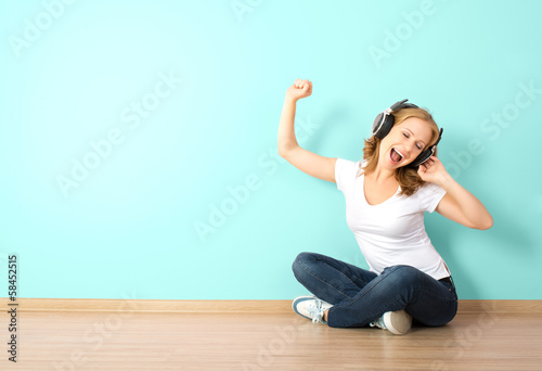 happy  woman in headphones listening to music in a room with a b
