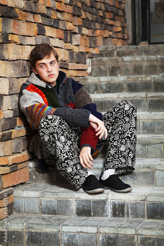 Young rastafarian man sitting on the steps